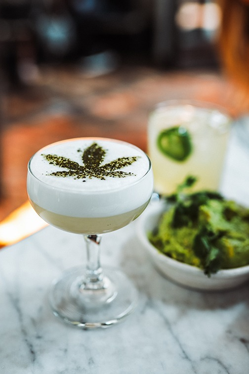 Cannabis-infused beverage with a cannabis leaf design on foam top